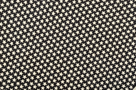 estrellas cinco puntas: White five-pointed stars on black fabric. Many white stars as a background. Foto de archivo