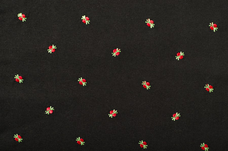 sewn: Small red floral pattern on black fabric. Hand sewn flowers on material as background. Stock Photo