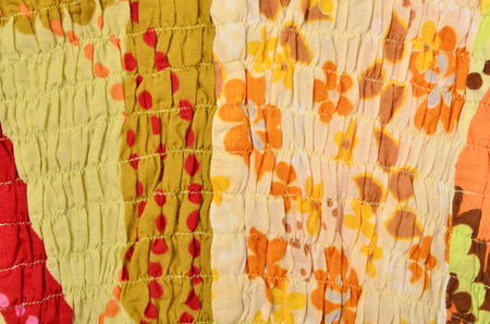 elastic garments: Close up on colored fabric crumpled with elastic. Flower material sewn with elastic as a background.