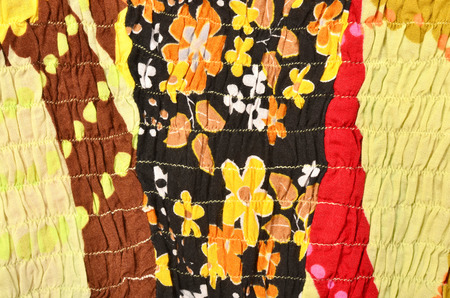 sewn up: Close up on colored fabric crumpled with elastic. Flower material sewn with elastic as a background.
