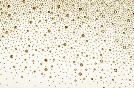 Gold rhinestones on fabric. White fabric decorated with gold jewels as background. Standard-Bild