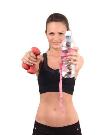 bebes niñas: Deportes y la hidratación. Muchacha hermosa del ajuste en la celebración de pesas delanteras y una botella de agua envuelta con un centímetro. Falta de definición en el modelo, se centran en la botella. Aislado en blanco.