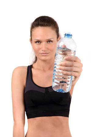 bebes niñas: La hidratación es importante. Muchacha que sostiene una botella de agua que ofrece a beber. La falta de definición en el modelo, se centran en la botella. Aislado en blanco. Foto de archivo