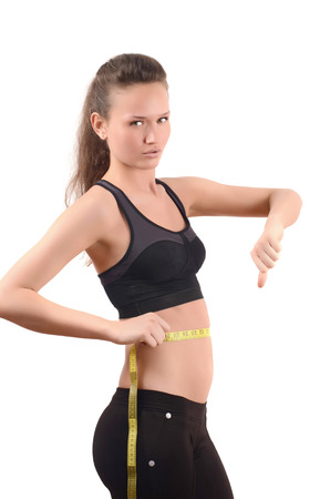 waist down: Beautiful fit girl sad measuring her waist with a measuring tape in inch. Thumbs down. Isolated on white.