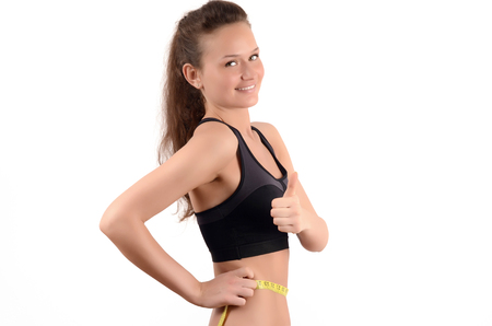 profile measurement: Thumbs up. Profile of a beautiful fit girl measuring her waist with a yellow measuring tape in inch. Isolated on white.