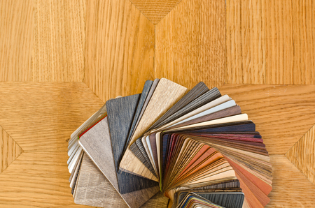 redecorating: Different color samples of wood floor on brown parquet background. Wooden color swatch fan to choose when redecorating.