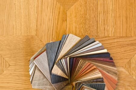 Verschillende kleuren monsters van houten vloer op bruine parket achtergrond. Houten kleurstaal fan om te kiezen wanneer het opknappen. Stockfoto