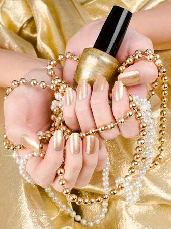 manicure nails: Close up on beautiful female hand with gold manicure.