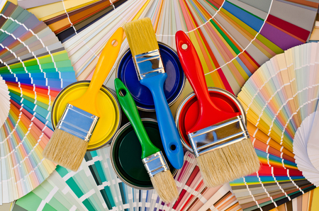 Paint cans and brushes on stripes of color swatches. Sample of colorful paint. Cans of red, yellow, blue and green paint.