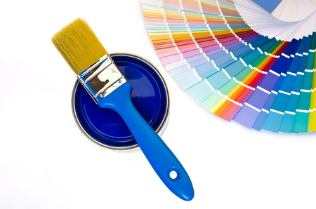 redecorating: Blue paint and swatch. Samples with different shades of blue and can of blue paint with a brush. Focus on the can. Isolated on white background.