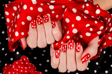 red nail colour: Close up on beautiful female hands with cute red manicure with white dots. Black dotted background.