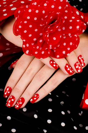 french manicure sexy woman: Close up on beautiful female hands with cute red manicure with white dots. Black dotted background.