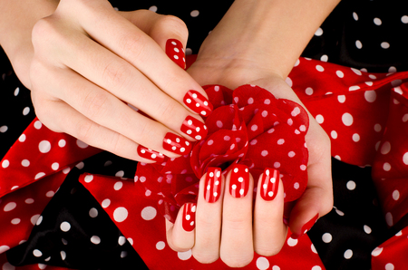 french manicure sexy woman: Close up on beautiful female hands with cute red manicure with white dots. Black and red dotted background.