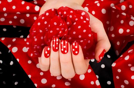 french manicure sexy woman: Close up on beautiful female hand with cute red manicure with white dots. Black and red dotted background. Stock Photo