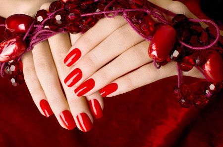 Close up on beautiful female hands with sexy red manicure. Red velvet background.