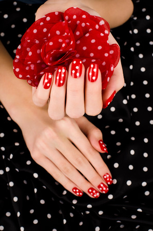 red nail colour: Close up on beautiful female hand with cute red manicure with white dots. Black dotted background.