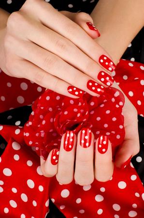 manicura: Cierre en hermosas manos femeninas con linda manicura roja con puntos blancos. Negro y rojo fondo punteado. Foto de archivo