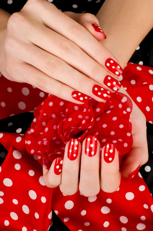 red nail colour: Close up on beautiful female hands with cute red manicure with white dots. Black and red dotted background.
