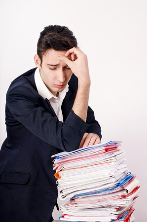 unsatisfied: Worried business man with a lot of paper work. Unhappy worker with a big pile of files to work on. Stock Photo