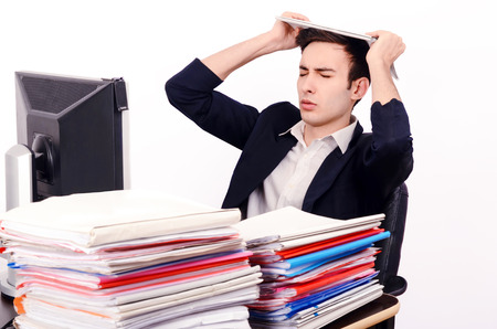 unhappy worker: Worried business man with a lot of work. Unhappy worker with a big pile of files to work on. Stock Photo