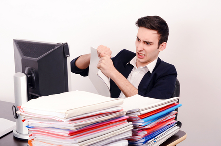 quiting: Angry business man tearing up paper work.Unhappy worker with a big pile of files to work on. Stock Photo