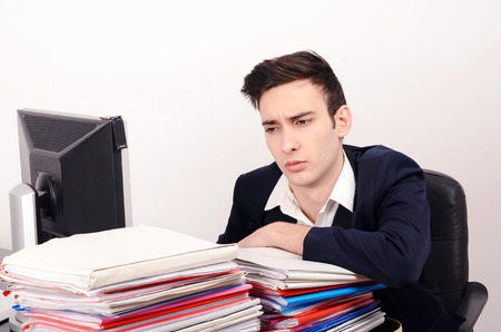 unhappy worker: Bored and worried business man with a lot of work. Unhappy worker with a big pile of files to work on.