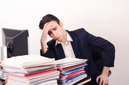 Worried business man with a lot of work. Unhappy worker with a big pile of files to work on. Фото со стока