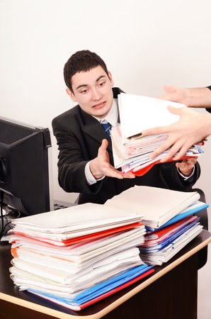 unhappy worker: Desperate business man receiving a lot of paper work. Unhappy worker with a big pile of files to work on. Stock Photo