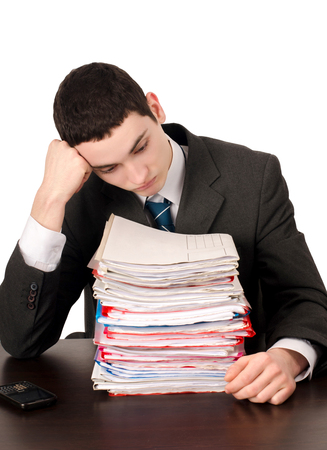 unhappy worker: Bored business man with a lot of work. Unhappy worker with a big pile of files to work on. Isolated on white.