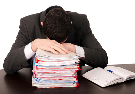 exhausted worker: Tired business man sleeping at work. Exhausted worker sleeping on a pile of files. Isolated on white.