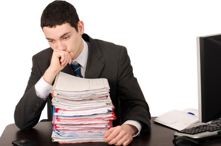 white work: Worried business man with a lot of work. Unhappy worker with a big pile of files to work on. Isolated on white.