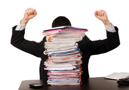 unhappy worker: Desperate business man with a lot of work. Unhappy worker with a big pile of files to work on. Isolated on white. Stock Photo