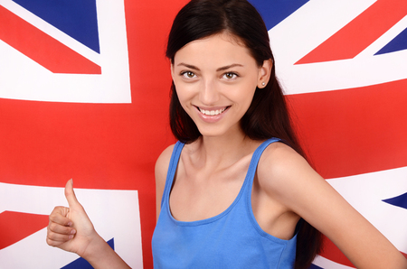 british girl: Portrait of a beautiful British girl smiling and signing thumbs up. Young woman standing with the UK flag in the background.