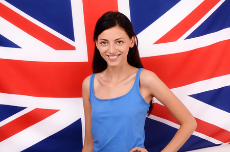 british girl: Portrait of a beautiful British girl smiling. Young woman standing with the UK flag in the background.