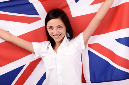 british girl: Portrait of a beautiful British girl smiling holding up the UK flag.