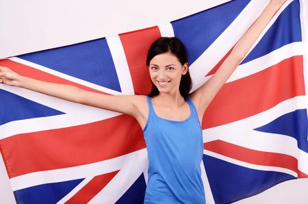 british girl: Beautiful British girl smiling holding up the UK flag. Stock Photo