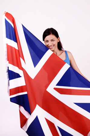 british girl: Beautiful British girl smiling holding up the UK flag looking to the side.