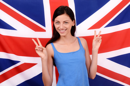british girl: Portrait of a beautiful British girl smiling and signing victory. Young woman standing with the UK flag in the background.