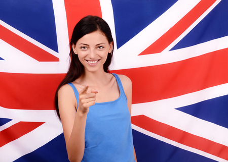 british girl: Portrait of a beautiful British girl smiling and pointing in front to you. Young woman standing with the UK flag in the background.