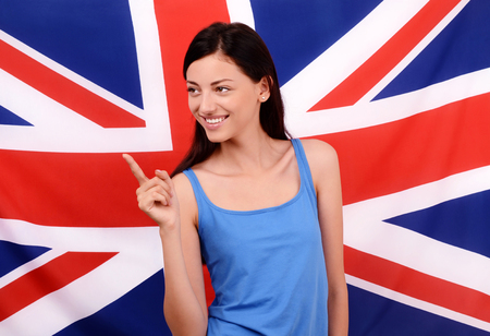 british girl: Portrait of a beautiful British girl smiling and pointing to the side. Young woman standing with the UK flag in the background. Stock Photo