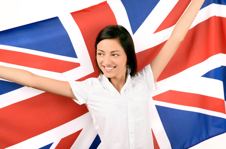 british girl: Portrait of a beautiful British girl smiling holding up the UK flag, looking away. Isolated on white.