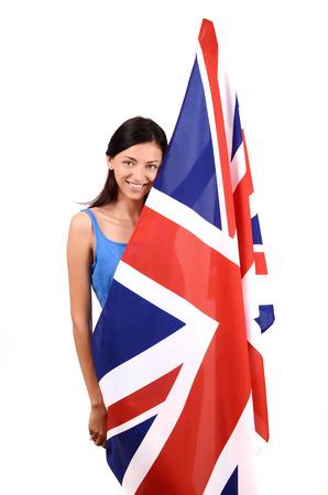 british girl: Portrait of a beautiful British girl smiling holding up the UK flag. Isolated on white.