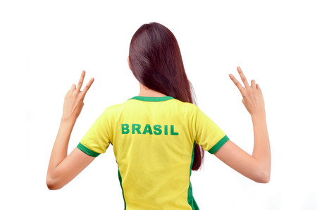 turned out: Girl signing victory for Brasil. Attractive girl with Brasil written on the back of her yellow t-shirt. Isolated on white.