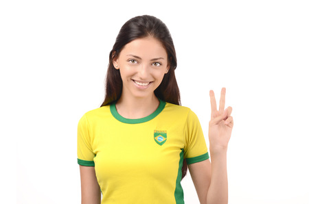 Girl signing victory for Brazil. Attractive girl with Brazilian flag on her yellow t-shirt. Isolated on white. Stock Photo