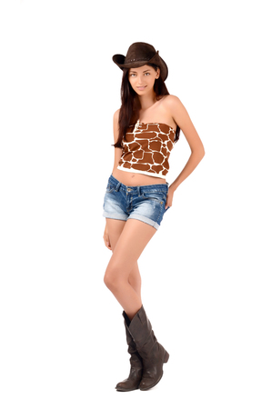 sexy cowboy: Sexy american cowgirl with shorts and boots and a cowboy hat. Isolated on white background. Stock Photo