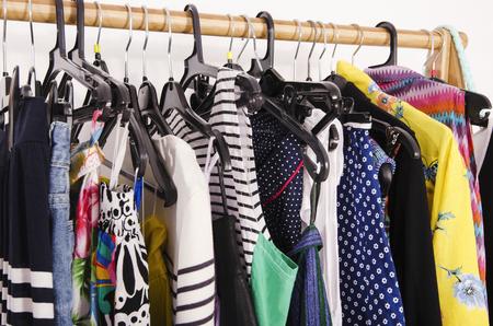 ropa de verano: Cierre en la ropa de colores en perchas en una tienda. Ropa y accesorios que cuelgan en un estante muy bien dispuestas.