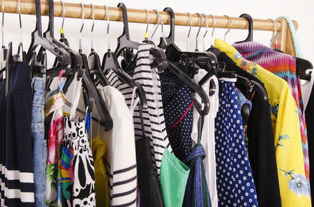 clothes hanging: Close up on colorful clothes on hangers in a store. Clothes and accessories hanging on a rack nicely arranged. Stock Photo