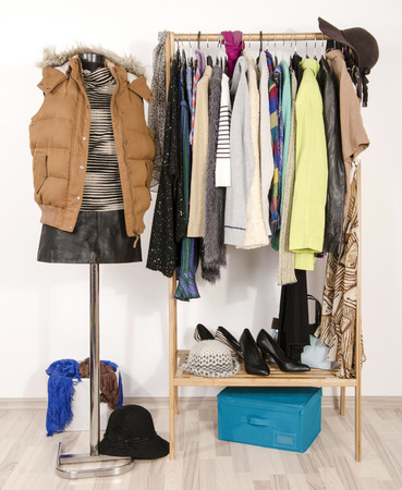 Wardrobe With Clothes Arranged On Hangers And A Winter Outfit On A  Mannequin. Dressing Closet
