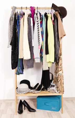 casual clothes: Close up on autumn winter clothes on hangers in a store. Colorful clothes and accessories hanging on a rack nicely arranged.