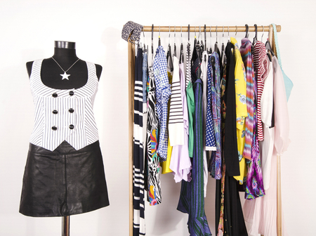 striped vest: Dressing closet with colorful clothes arranged on hangers and an outfit on a mannequin. Wardrobe with clothes and accessories. Tailors dummy wearing a striped vest and a black leather skirt.